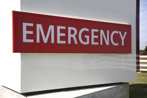 A red sign with white lettering on it saying emergency.