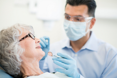 A elderly woman happy with her dentist.