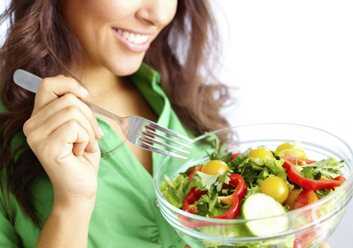 A woman on a diet eating a salad.